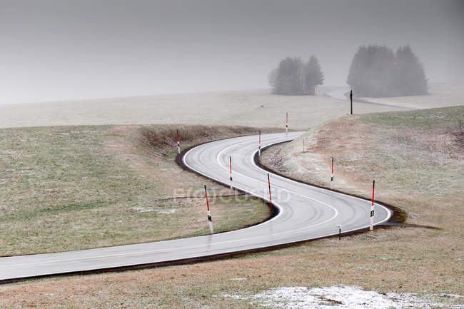 Paesaggio della campagna con strada asfaltata della curva in inverno — Foto stock