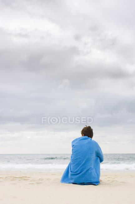 Vista posteriore di uomo solitario seduto sulla spiaggia e coperto di asciugamano blu — Foto stock
