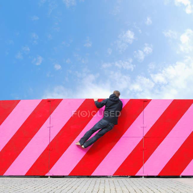 Vista posteriore di curioso uomo appeso il recinto muro spogliato — Foto stock