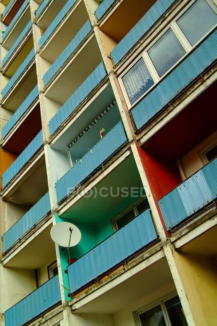 Casa residencial con balcones coloridos y ronda de antena de tv - foto de stock