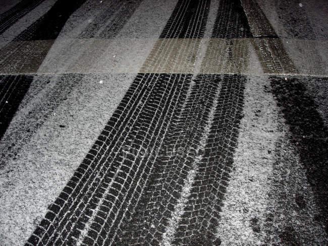 Strada di asfalto con tracce di ruote innevata — Foto stock