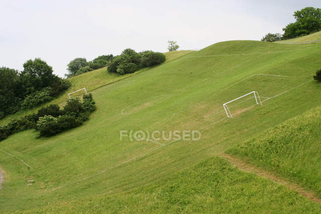 Terrain de soccer sur la colline du pré vert, buts de football — Photo de stock
