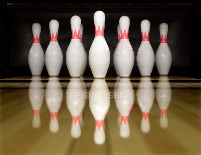White bowling cones on wooden shiny surface with reflection — Stock Photo