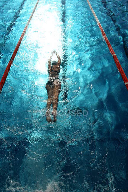 Sportive woman under pool water — Stock Photo
