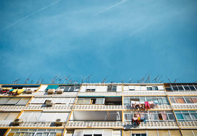 Building house with windows and balconies and blue clear sky — Stock Photo