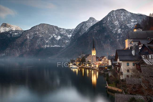Альпийские горы с озером в маленькой деревне Гальштат, освещенной церкви — стоковое фото