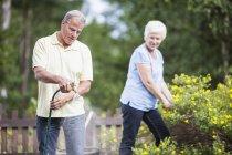Senior woman looking at man watering plants in garden — Stock Photo