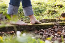 Low section of woman walks barefoot on log — Stock Photo