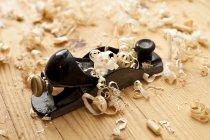Plaina com lascas de madeira no chão de madeira — Fotografia de Stock