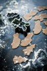 Blasse von figürlichen Cookies, bestreut mit Puderzucker auf schwarze Oberfläche — Stockfoto