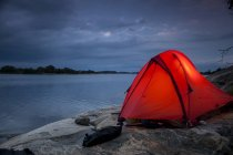 Tent on rock at lake shore during dusk — Stock Photo