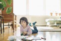 Junge mit bunten Filzstiften und Büchern liegt zu Hause auf dem Boden — Stockfoto