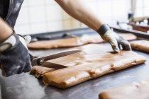 Immagine potata di caramello di taglio dell'operaio con le forbici in negozio di caramelle — Foto stock
