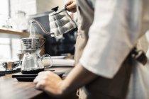 Abdomen vue côté de barista verser de l'eau bouillante dans le filtre à café — Photo de stock
