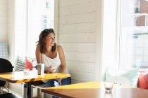 Menina adolescente feliz olhando para fora da janela do restaurante — Fotografia de Stock