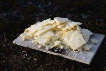 Fette di formaggio sulla scheda di legno al tavolo nero — Foto stock