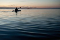Silhouette of man with paddle in kayak during sunset — Stock Photo