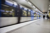 Railroad platform in subway and passing by train — Stock Photo