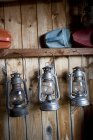 Oil lamps hanging on shelf against wooden wall — стокове фото