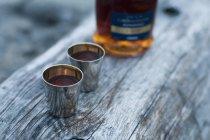 Vista de alto ângulo, de dois copos com a garrafa de álcool — Fotografia de Stock