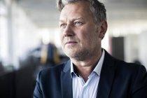 Homem de negócios maduro pensativo que olha afastado no escritório — Fotografia de Stock