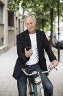 Uomo d'affari che utilizza il telefono cellulare mentre seduto in bicicletta sul marciapiede — Foto stock