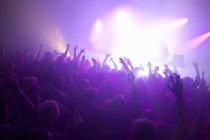 Raggi di viola faretti sopra la pista da ballo affollata al nightclub — Foto stock