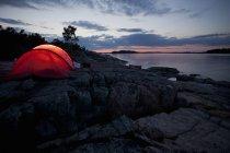 Купол палатки возле реки ночью — стоковое фото