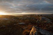 Vista panoramica del deserto pietroso e piccolo insediamento sotto il cielo nuvoloso — Foto stock