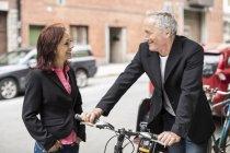 Uomo d'affari che tiene in mano il manubrio della bicicletta mentre comunica con la collega di strada — Foto stock