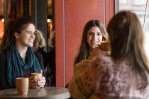 Glückliche Freundinnen am Cafétisch — Stockfoto