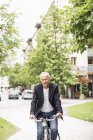 Ritratto di uomo d'affari maturo in bicicletta sulla strada — Foto stock