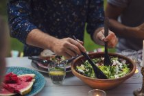 Midsection of man mixing salad at table during garden party — Stock Photo