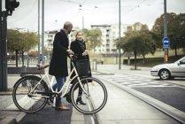 Uomini d'affari con bicicletta che attraversano la strada della città — Foto stock
