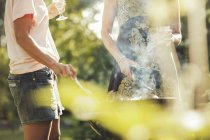 Midsection of women cooking on barbecue grill at back yard — Stock Photo