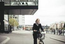 Sorridente donna d'affari metà adulto in bicicletta sulla strada della città — Foto stock