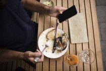 Міделю чоловік тримає мобільного телефону, а обідали дерев'яний стіл на тротуарі кафе — стокове фото
