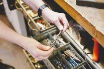 Cropped image du principal artisan tenant la mèche dans l'atelier de bijoux — Photo de stock