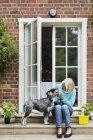 Щасливі старший жінка з собакою на вході в будинок — стокове фото