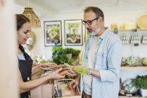 Reifer Mann kauft Karotten bei Verkäuferin im Lebensmittelgeschäft — Stockfoto