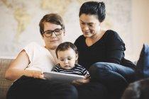 Femmes avec tout-petit regardant dans la tablette numérique tout en étant assis à la maison — Photo de stock