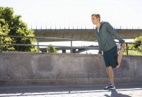 Full length of man doing stretching exercise on bridge — Stock Photo