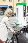 Smiling senior woman filling car with petrol at gas station — Stock Photo