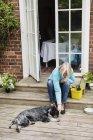 Senior woman stroking dog lying at house entrance — Stock Photo