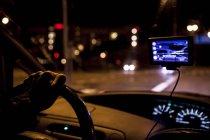 Imagen recortada del hombre conduciendo coche por la noche - foto de stock