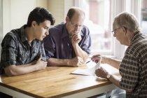 Família discutindo sobre o documento na mesa — Fotografia de Stock