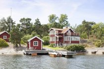 Красные деревянные дома и деревья на берегу озера — стоковое фото