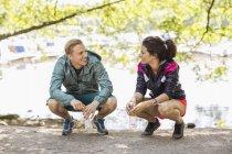 Longitud total de forma pareja conversando con botellas de agua mientras agachado por el lago - foto de stock