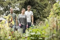 Friends looking at plants in garden — Stock Photo