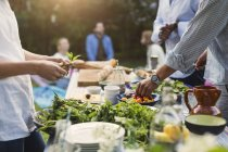 Midsection of friends preparing food at dining table in backyard — Stock Photo